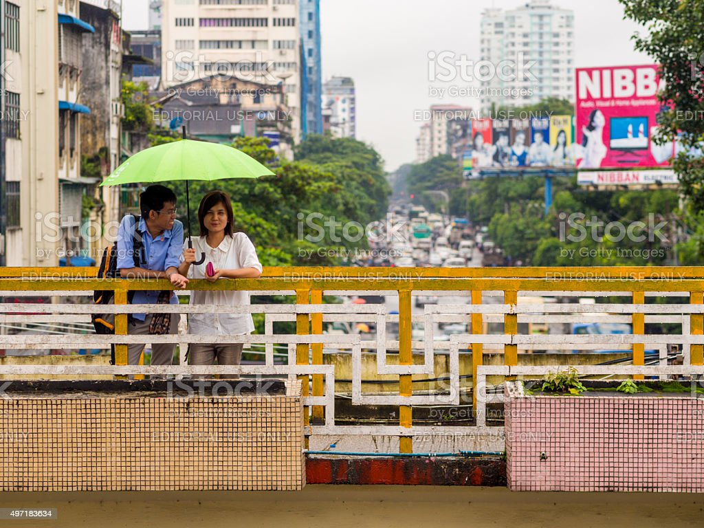Two share an umbrella in Yangon, Myanmar stock photo