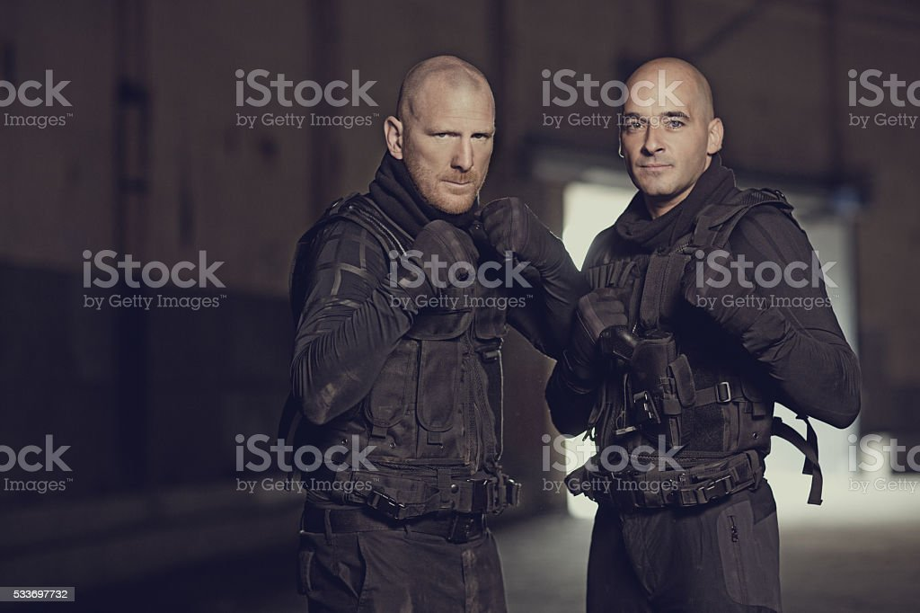Two shaven headed swat team members posing in abandoned warehouse stock photo