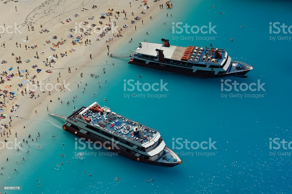Two ships at anchor, and the crowd of bathers royalty-free stock photo