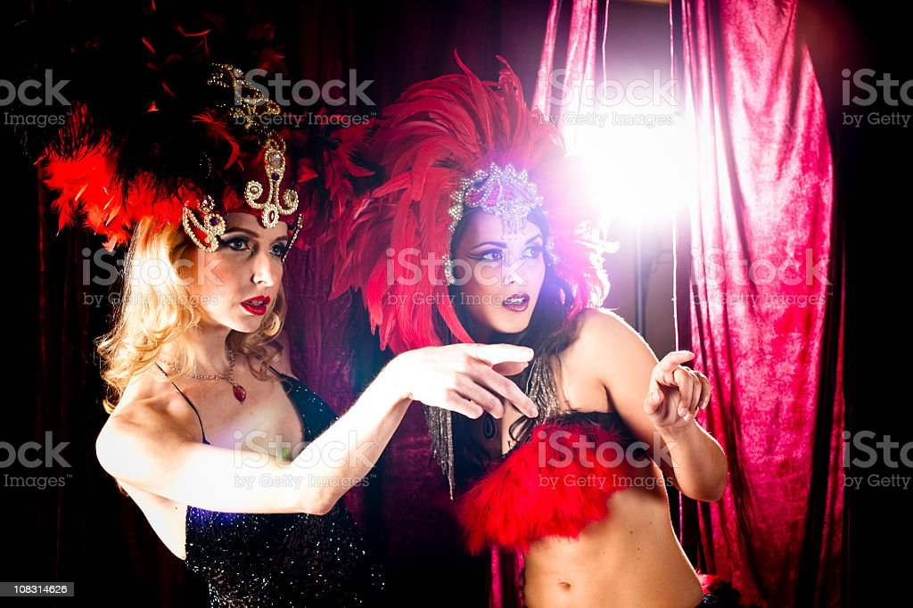 Two showgirls on stage, pointing to right stock photo