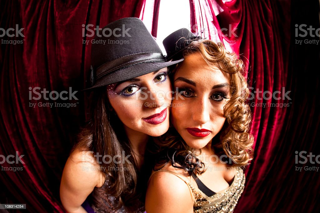 Two showgirls with stage curtains in background. royalty-free stock photo