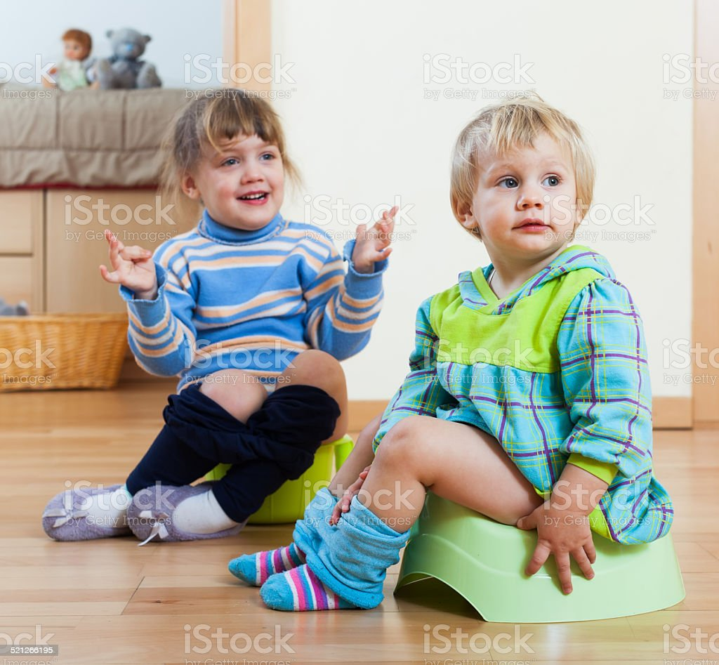 Two  siblings sitting on chamber pots stock photo