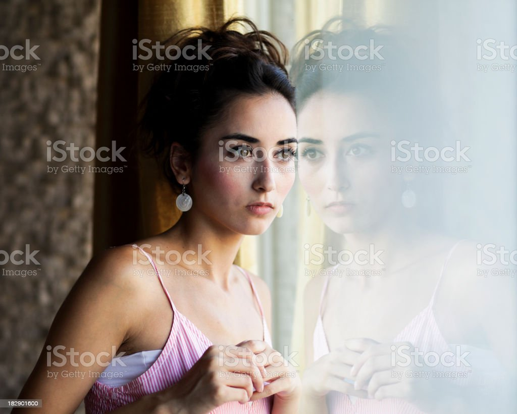 \'Young woman thinking front of a window, reflections on the...