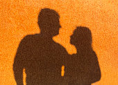 Two silhouettes on a rusty wall