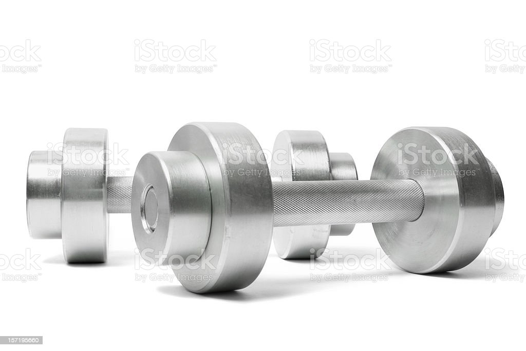 Two silver dumbbells sitting on a white table royalty-free stock photo