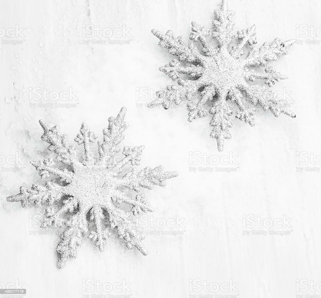 Snowflakes ornaments - Two Silver Glittered Snowflakes Ornaments In The Snow Royalty Free Stock Photo