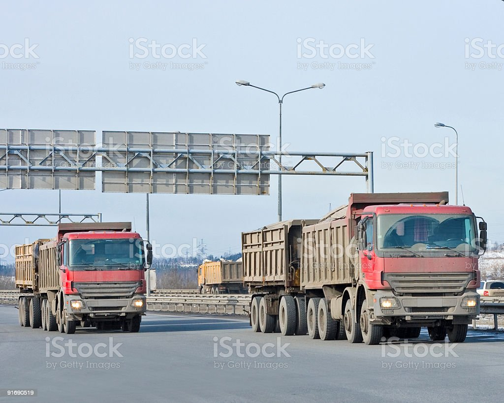 Two similar red dump trucks ride together royalty-free stock photo