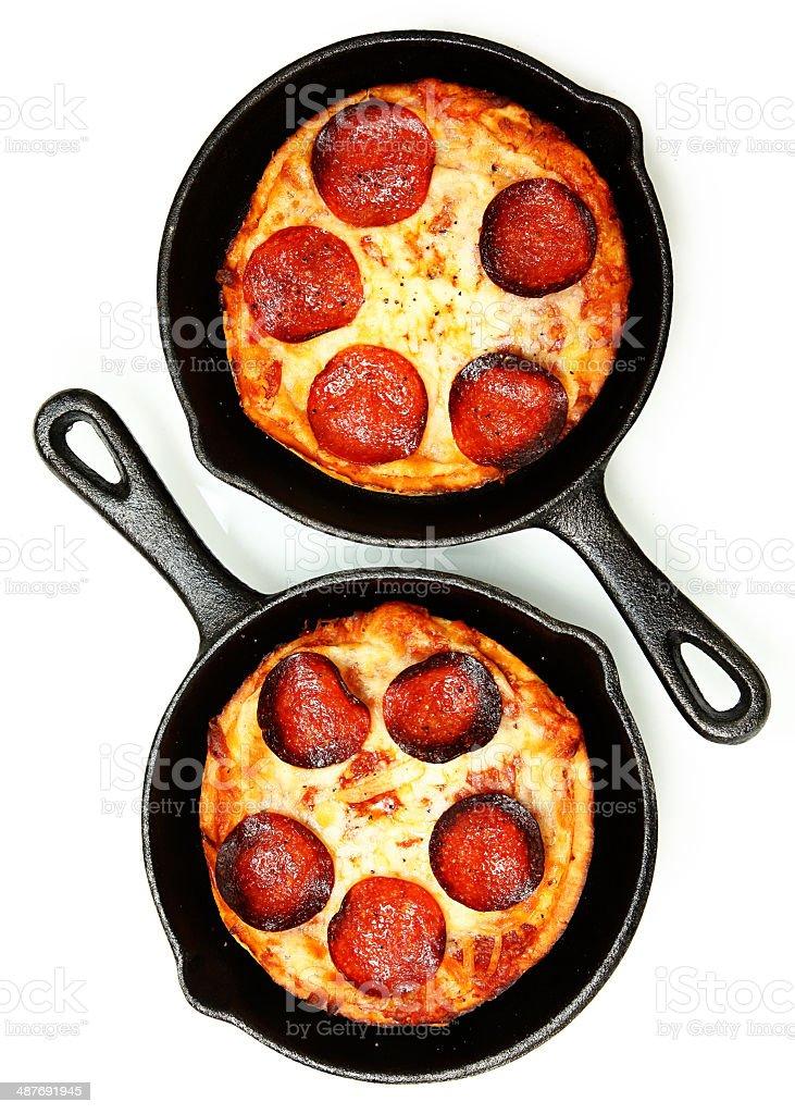 Two Single Serve Skillet Peperonni Pizzas Over White stock photo