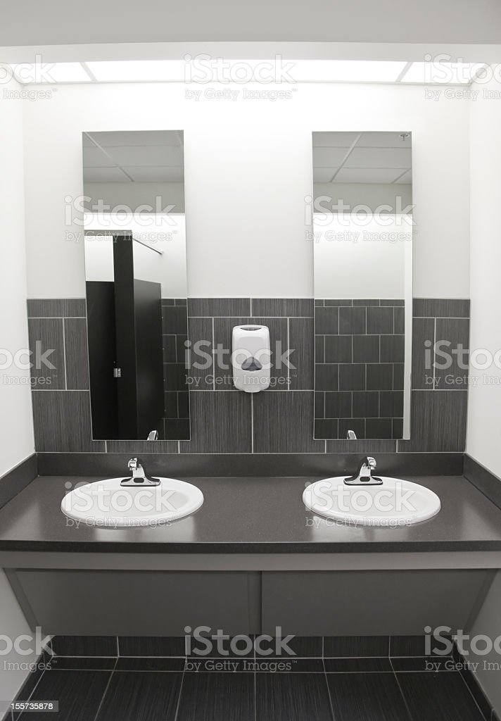 Two sinks and mirrors in a white and gray public restroom royalty-free stock photo