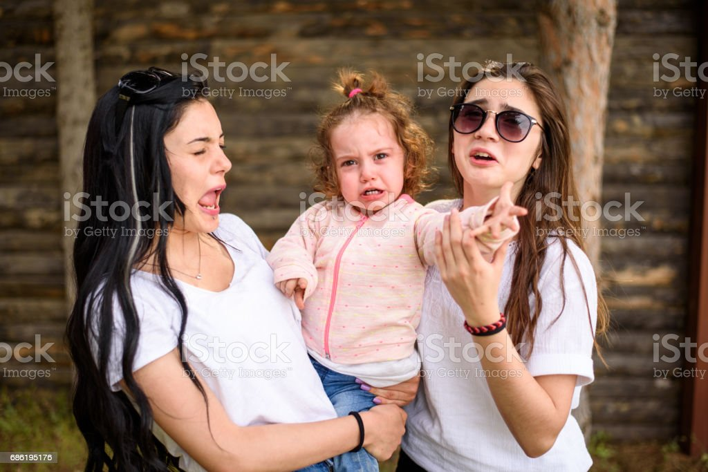 Two sister holding her anger little baby girl stock photo