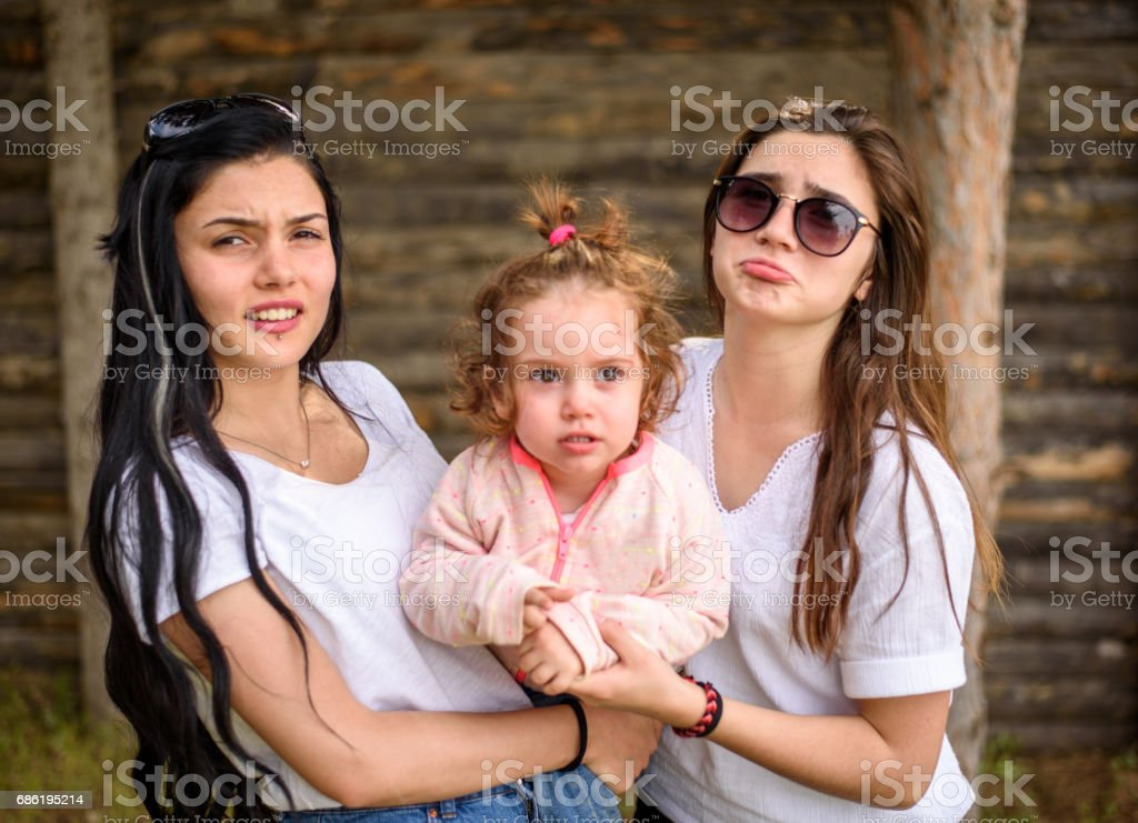 Two sister holding her little baby girl stock photo