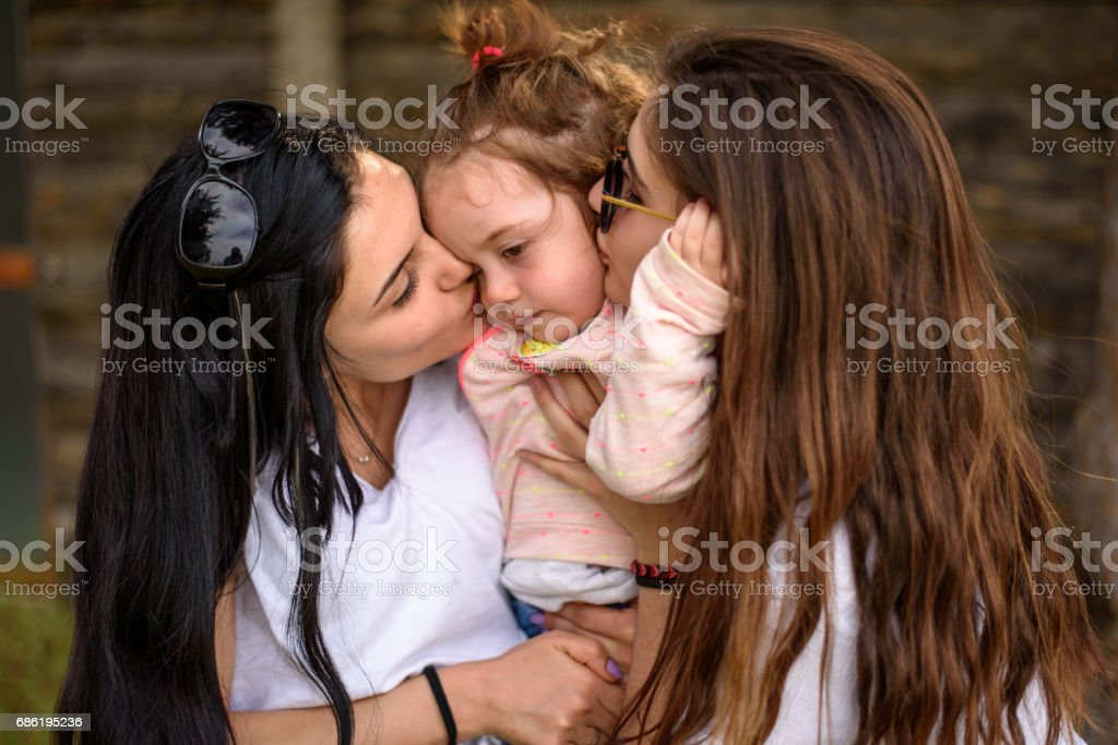Two sister kissing her little baby girl stock photo