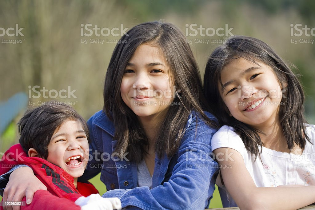 Two sisters and their disabled brother  at park, royalty-free stock photo