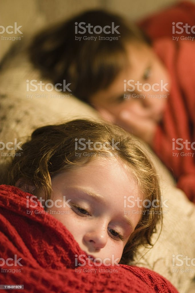Two sisters asleep under red covers. royalty-free stock photo