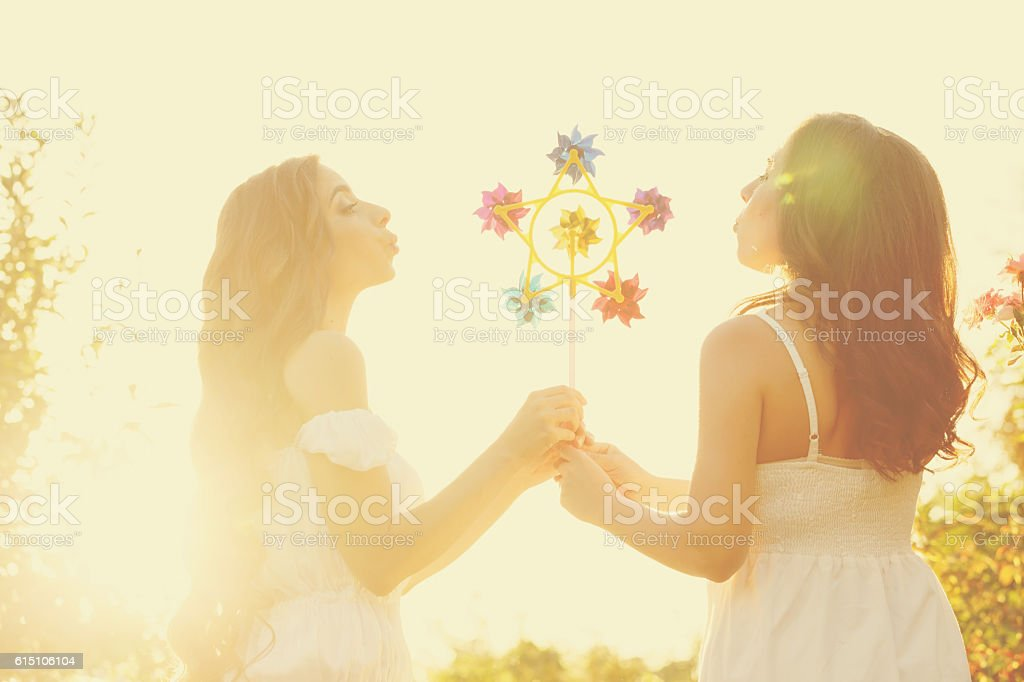 Two sisters blowing on whizzer stock photo