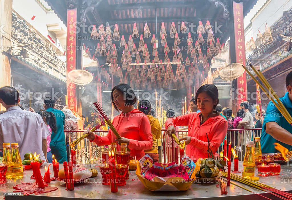 Two sisters burned incense worship Buddha Lunar New Year stock photo