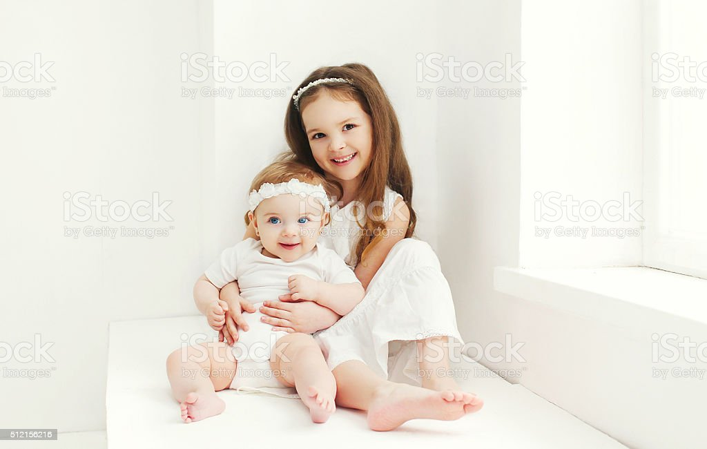 Two sisters children playing together at home in white room stock photo