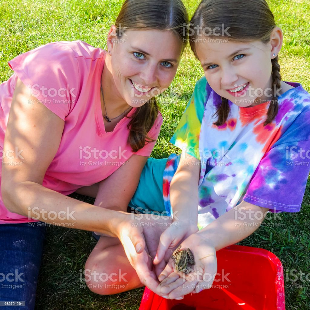 Two Sisters Happily Showing off the Leopard Frog They Caught stock photo