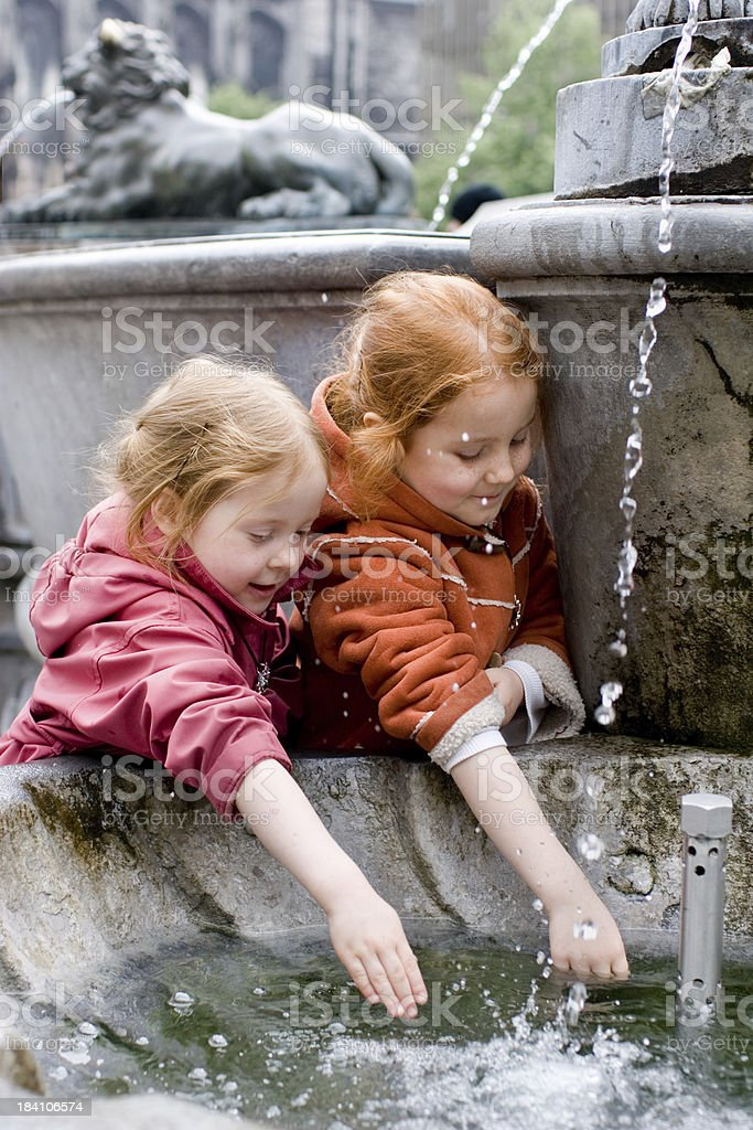 Two sisters having fun with a fountain royalty-free stock photo