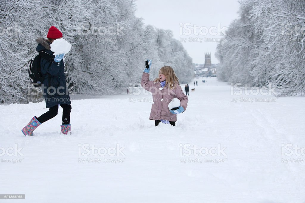 Two sisters having having a snowball fight stock photo