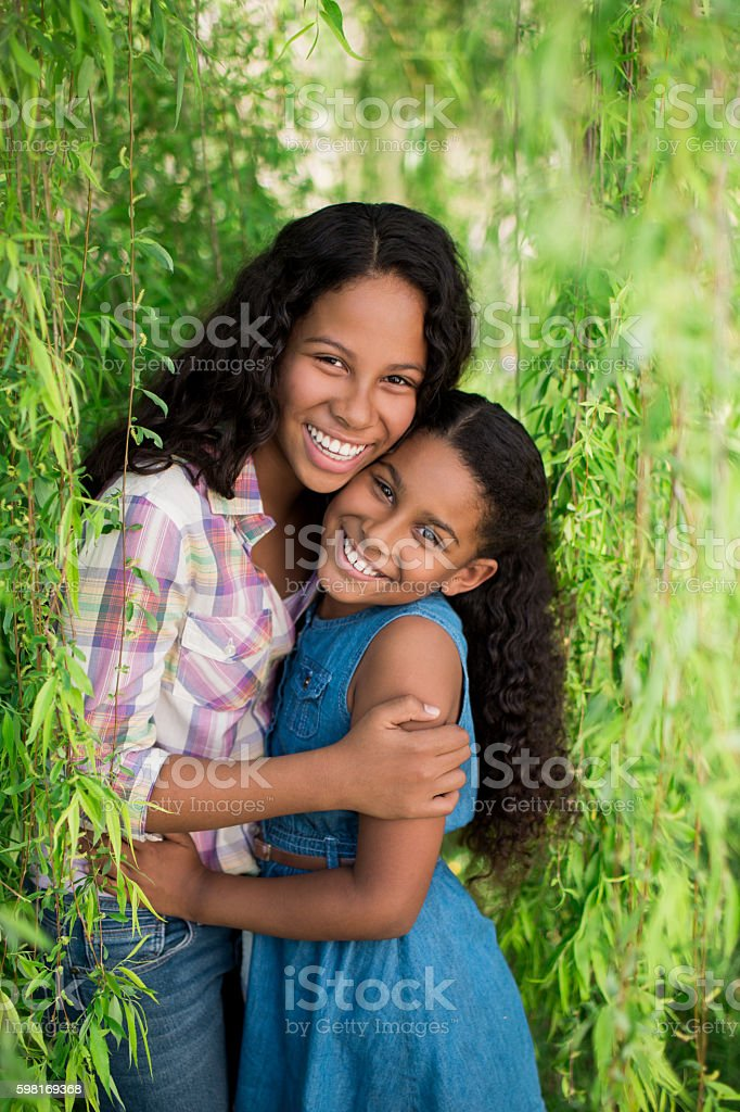 Two sisters hugging and smiling at camera stock photo