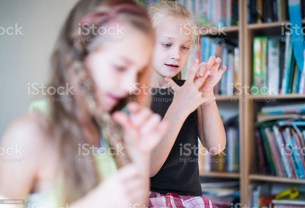 Two sisters in kids room, oldest sister make hair dress. stock photo