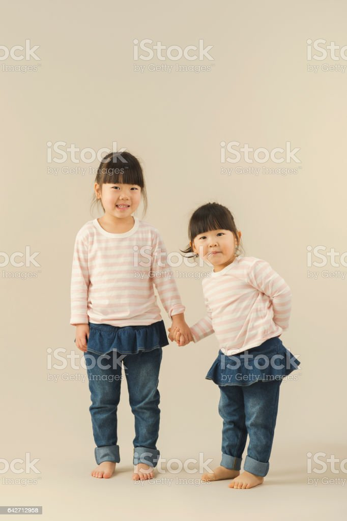 Two sisters in studio shot stock photo