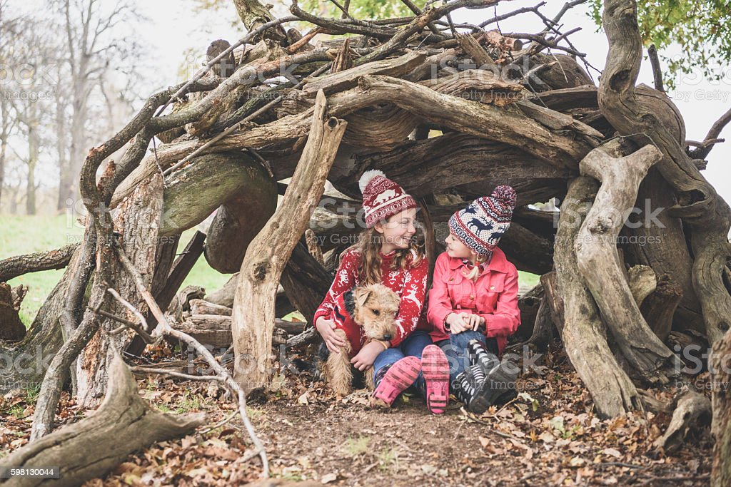 Two sisters in winter clothes in log den with dog stock photo