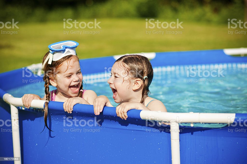 Two Sisters Laughing in a Swimming Pool royalty-free stock photo