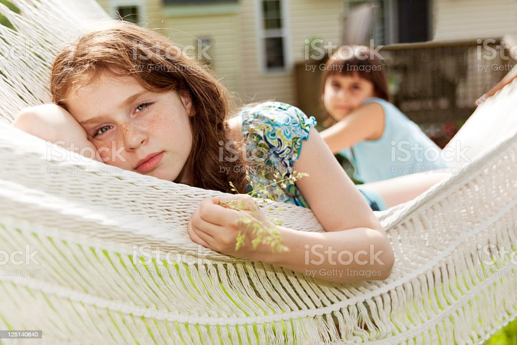 Two sisters lying down in the hammock stock photo