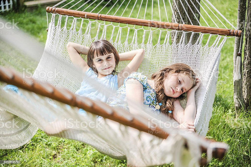 Two sisters lying down in the hammock royalty-free stock photo