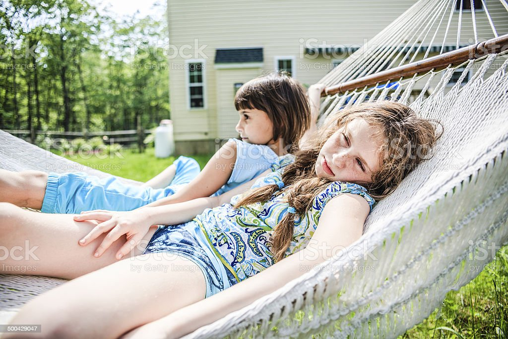 Two sisters lying down on a hammock. royalty-free stock photo