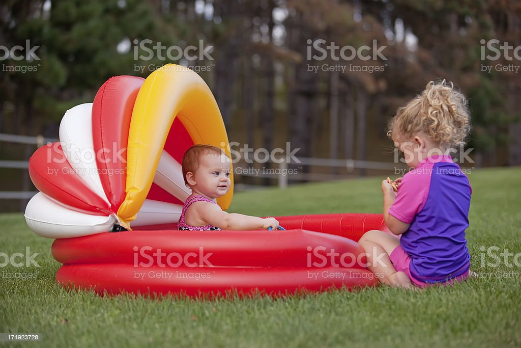 Two Sisters Playing by Swimming Pool stock photo