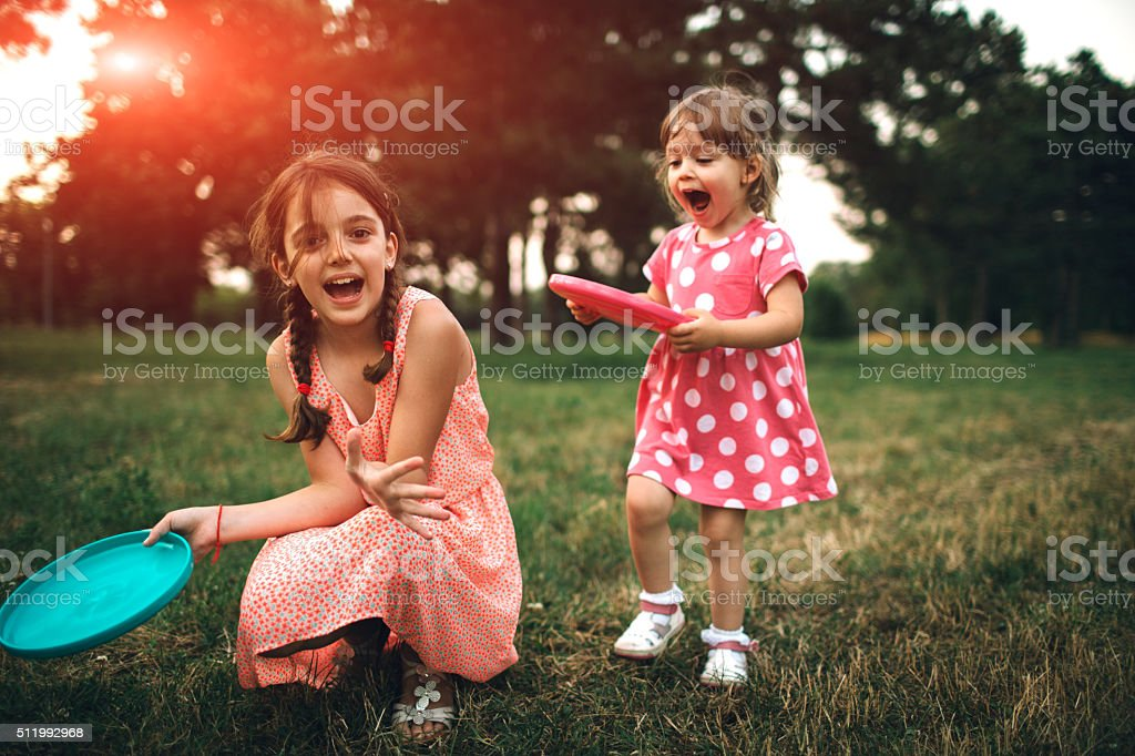 Two Sisters Playing Frisbee On Picnic stock photo