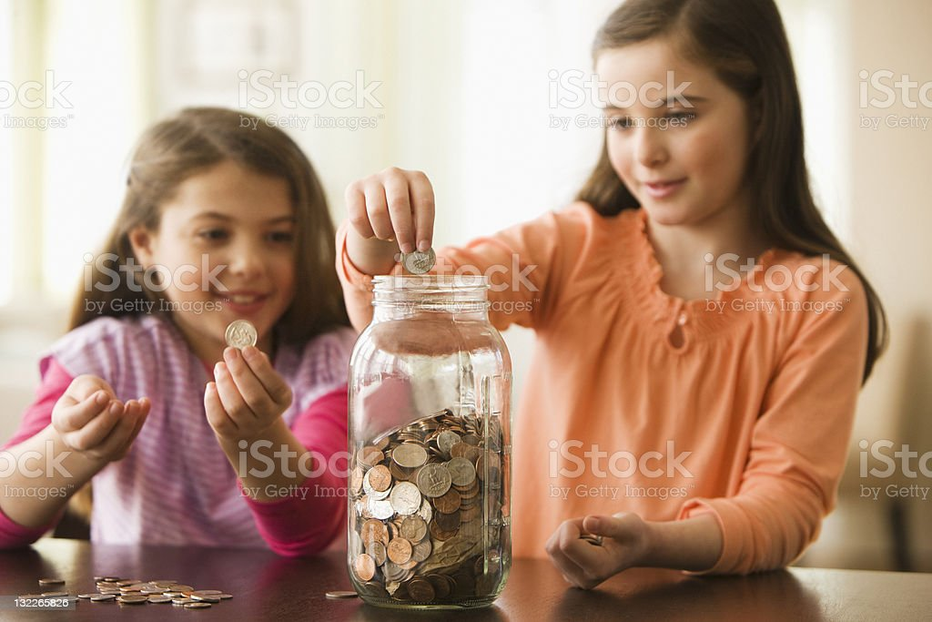 Two Sisters putting coins in a jar stock photo