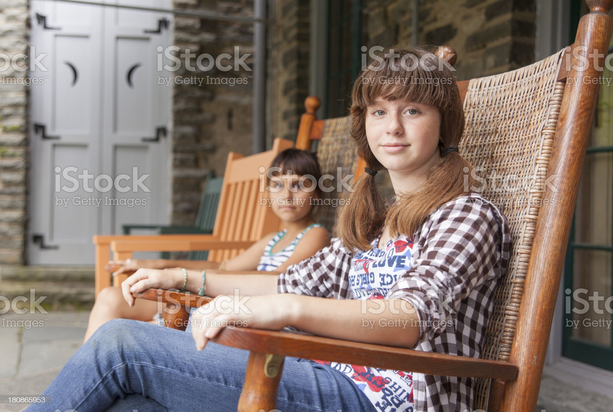 Two sisters relaxing on the open verandah royalty-free stock photo