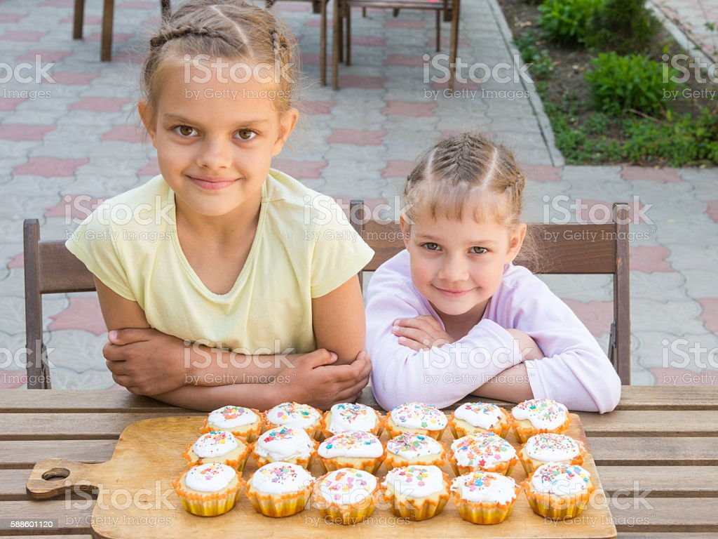 Two sisters sitting at a table on which are freshly stock photo