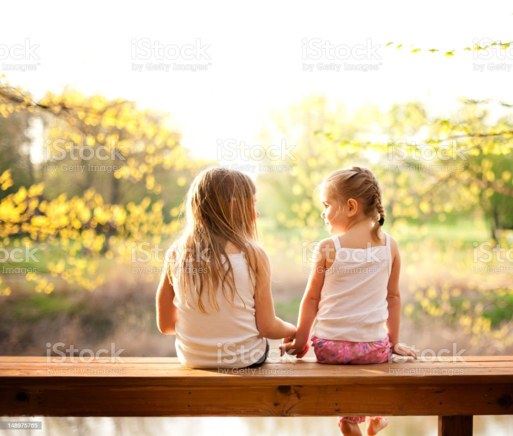 Two Sisters Sitting Together in the Evening Sun stock photo