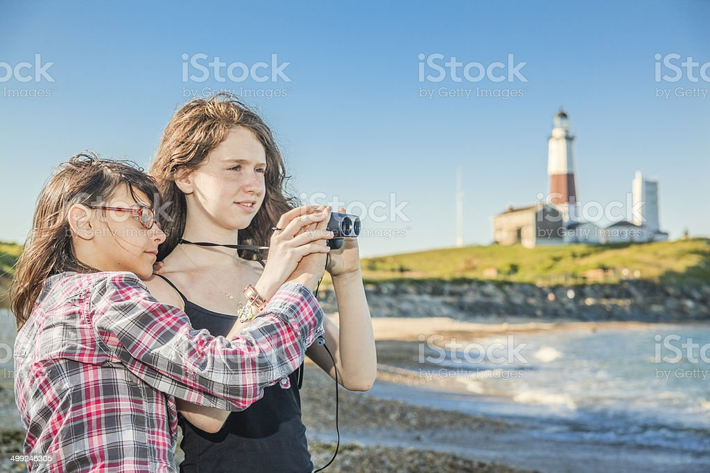 Two sisters, teenager girls, exploring ocean with binocular royalty-free stock photo