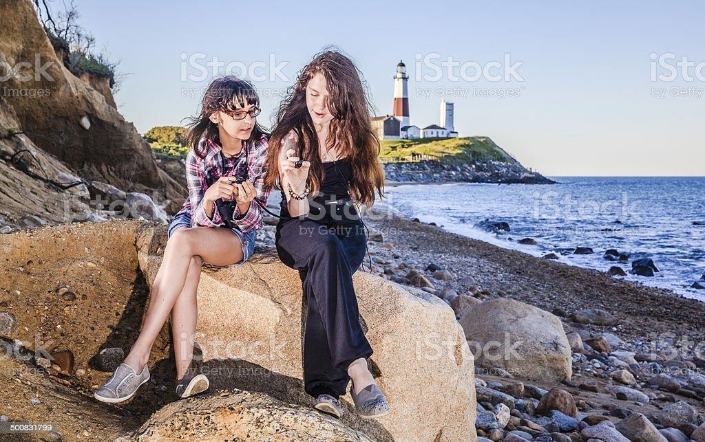 Two sisters, teenager girls, exploring ocean with binocular royalty-free stock photo