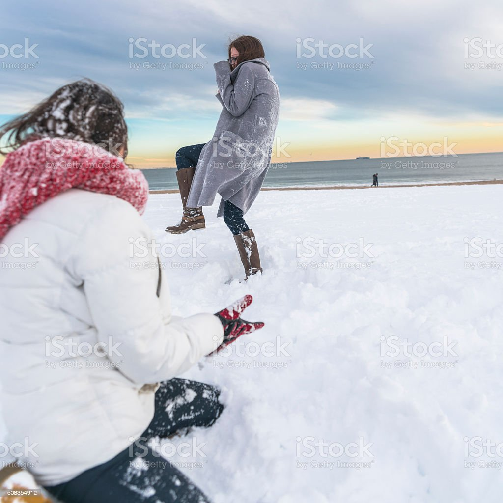 Two sisters, teenager girls, play snowballs at the Brighton Beach stock photo