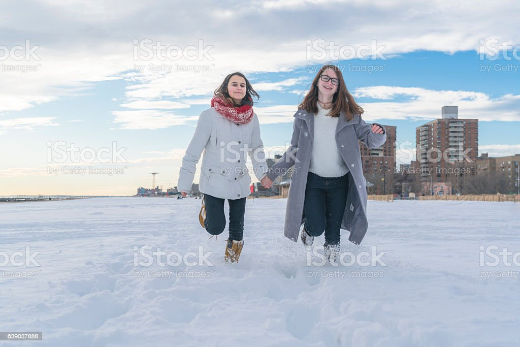 Two sisters, teenager girls, run on the beach stock photo
