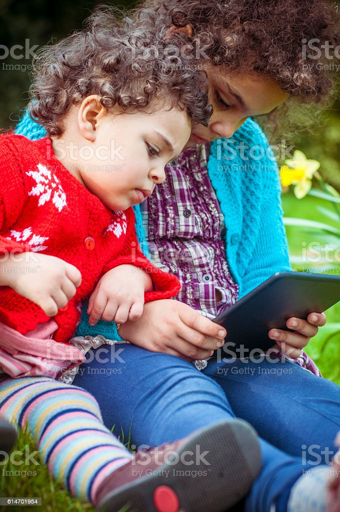 PEOPLE: Two Sisters Using Digital Tablet in Park stock photo