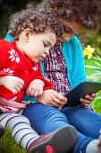 PEOPLE: Two Sisters Using Digital Tablet in Park