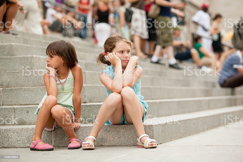 two sisters waiting on the stairs of public building stock photo