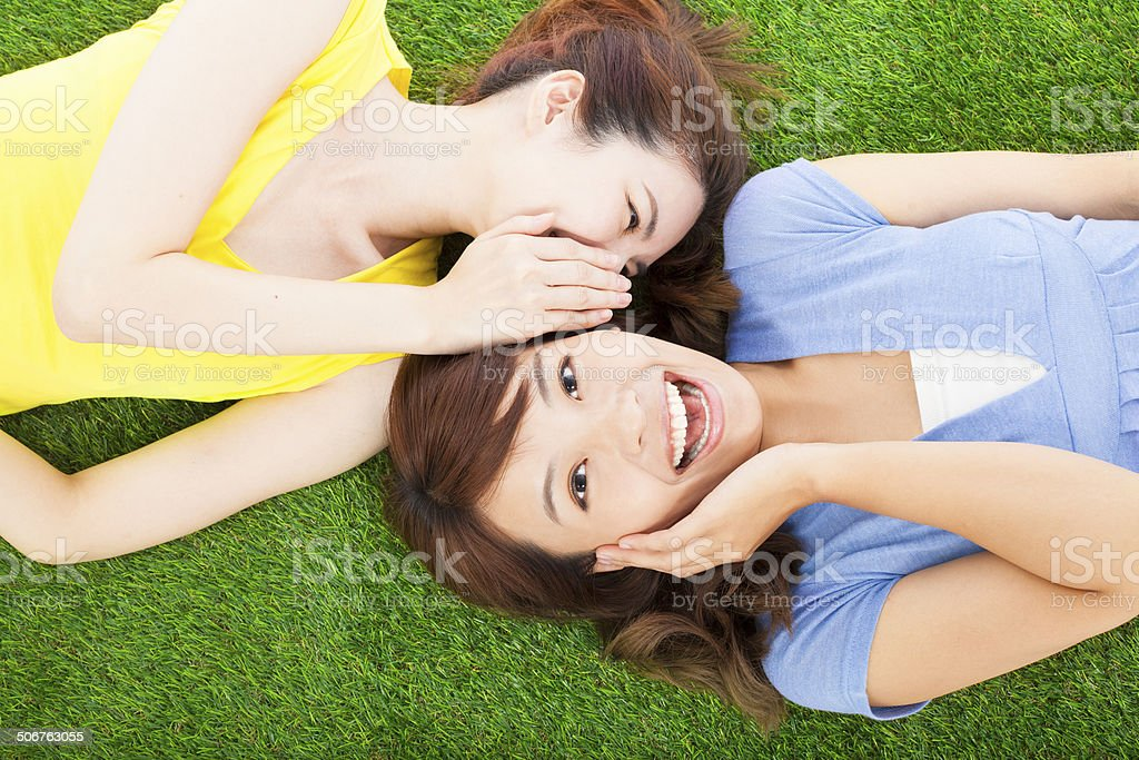 two sisters  whispering gossip on the grass stock photo