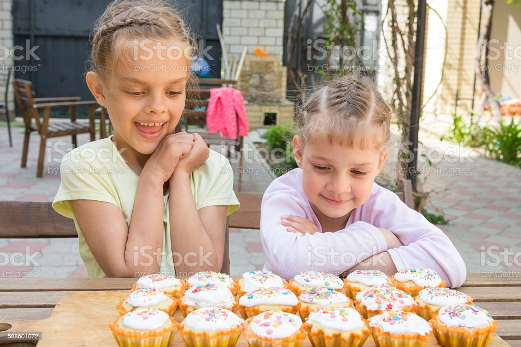 Two sisters with an appetite for looking at home-baked Easter stock photo