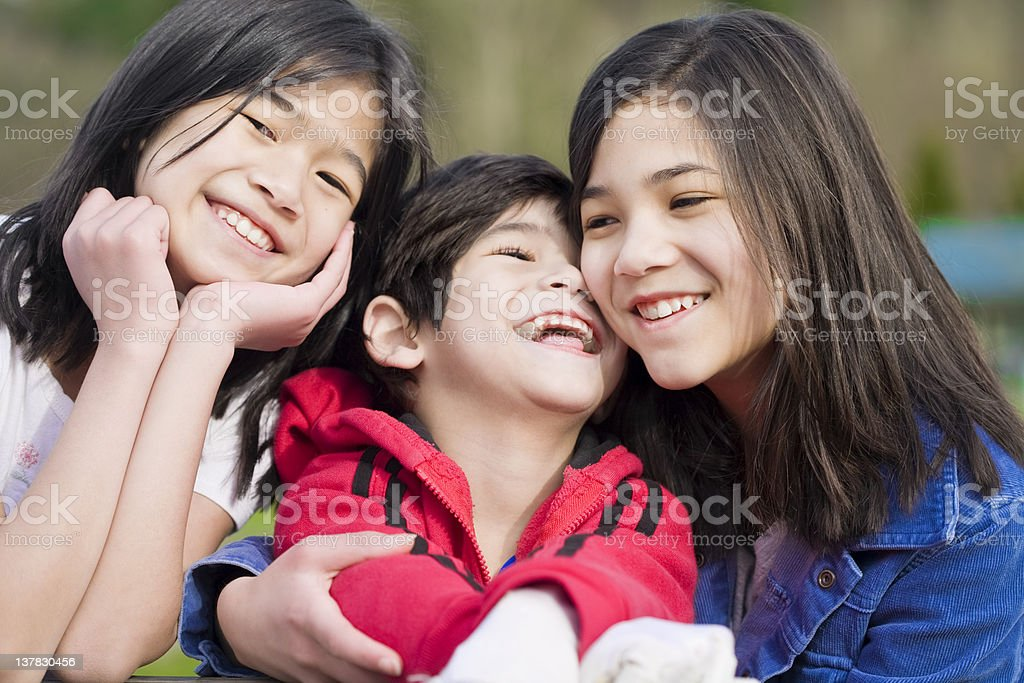Two sisters with disabled brother at park stock photo