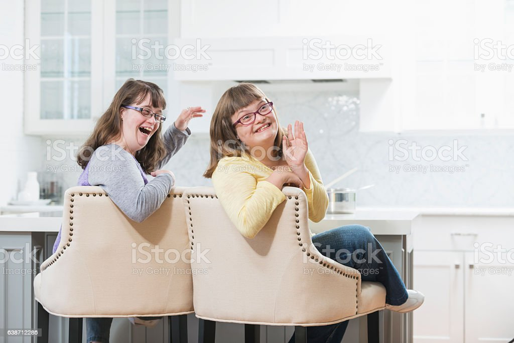 Two sisters with down syndrome at home stock photo