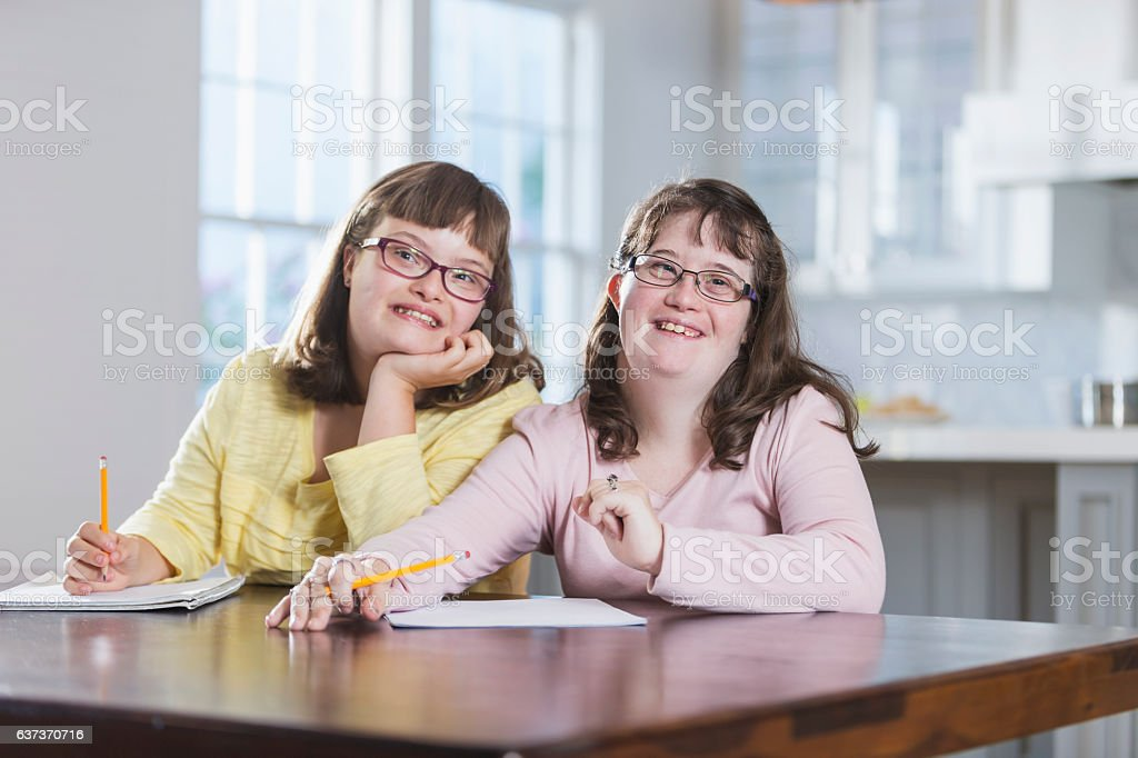 Two sisters with down syndrome, doing homework stock photo